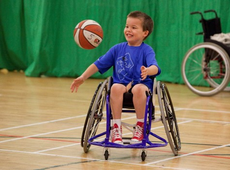 Kids with disabilities play adapted sports like this kid playing basketball.