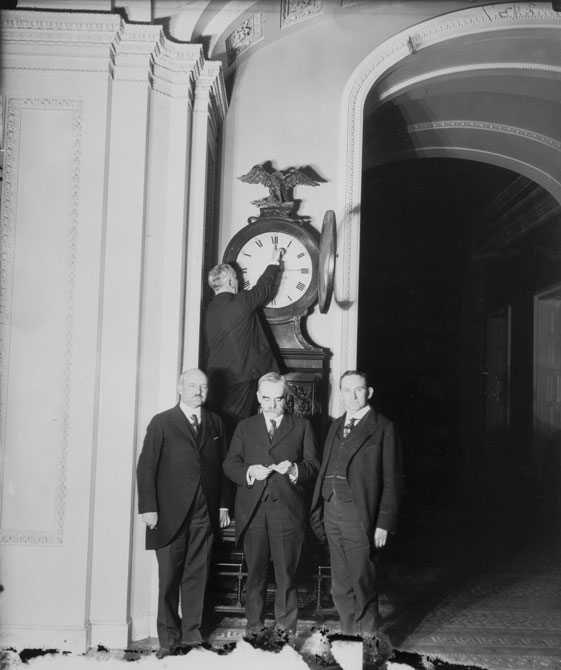 Senate+Sergeant+at+Arms+Charles+P.+Higgins+turns+forward+the+Ohio+Clock+for+the+first+Daylight+Saving+Time%2C+while+Senators+William+M.+Calder+%28NY%29%2C+Willard+Saulsbury%2C+Jr.+%28DE%29%2C+and+Joseph+T.+Robinson+%28AR%29+look+on%2C+1918.+Credit%3A+Public+Domain
